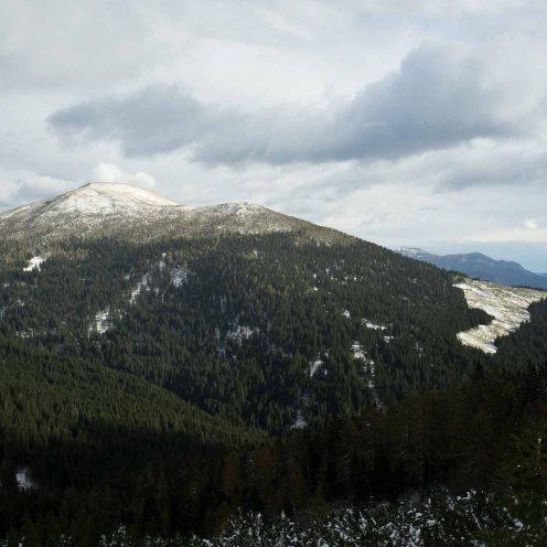 Salendo sul sentiero, la vista sulla Cima dei Paradisi da poco innevata e, in basso a destra, i prati della Malga Fossernica di dentro